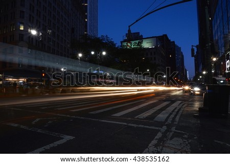 New York City, NY - June 7, 2016: Traffic travels on 6th avenue in midtown manhattan through a long exposure photo during the night commute - stock photo