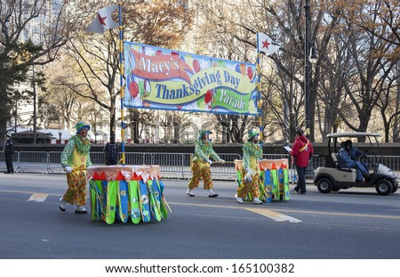 NEW YORK CITY, NY - NOVEMBER 28 : Clowns pushing parade sign through W 59th ST during the Macy's 87th Annual Thanksgiving Day Parade on November 28, 2013 in New York City, New York.  - stock photo