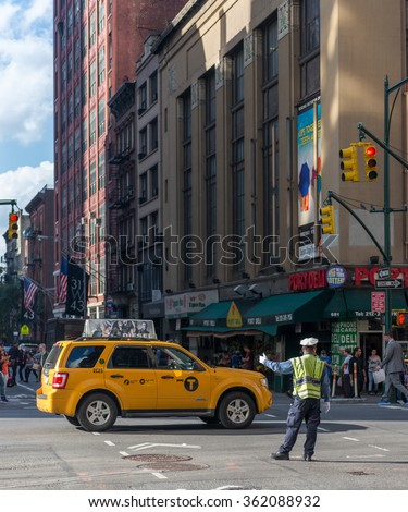 NEW YORK CITY, NY/USA - OCTOBER 16TH, 2014:  A traffic police man is redirecting the traffic at W 42nd St Ave during an intervention in Times Square area, October 16th, 2014, New York City, NY, USA.