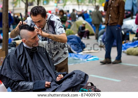 NEW YORK CITY - OCT. 21:  Unidentified man receives a barber haircut at Occupy Wall Street demonstration in NYC's Zuccotti Park on Oct 21, 2011.  The protest began on Sept 17. - stock photo