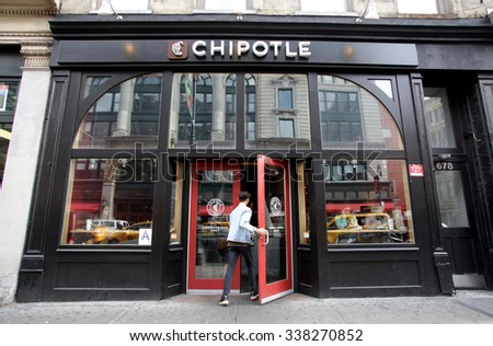 NEW YORK CITY - OCTOBER 22, 2015: Pedestrians walk past a Chipotle Mexican fast food restaurant. Chipotle Mexican Grill, Inc. is a chain of restaurants. - stock photo