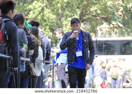 NEW YORK CITY - SEPTEMBER 19: An Apple Store associate sips coffee to stay awake while monitoring the crowd of people lined up to purchase the new iPhone 6 on September 19, 2014 in New York, NY. - stock photo