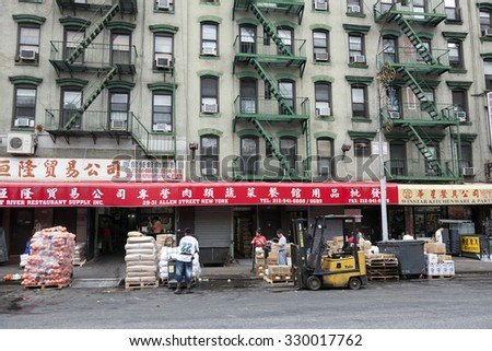 new york city, 11 september 2015: hard working people in front of shops on allen street in chinatown manhattan new york city - stock photo
