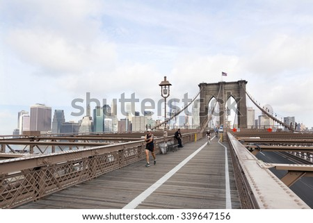 New York City, 13 september 2015: people engaged in bike run and others running on brooklyn bridge new york with manhattan in the background