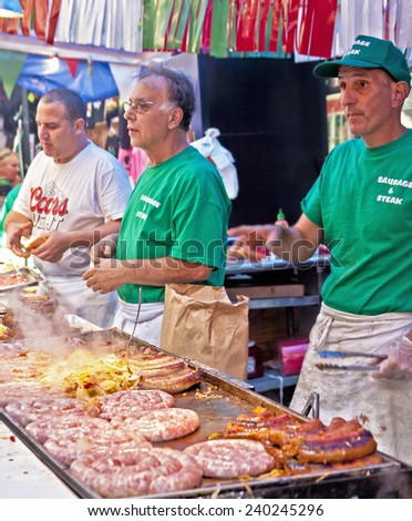 NEW YORK CITY - SEPTEMBER 22: Vendors cooking and serving food at the San Gennaro festival in New York City on September 22, 2013.  - stock photo