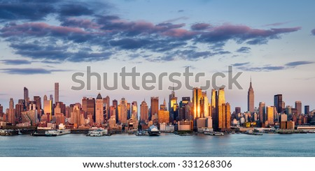 New York City skyline across the Hudson River. The Midtown Manhattan skyscrapers reflect the sunset light.