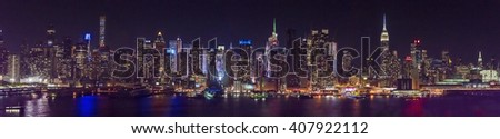 New York city skyline at night time,  displaying colorful lights on its skyscraper. - stock photo
