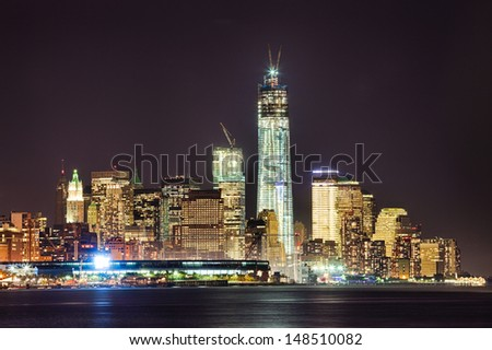 New York City skyline at night w the Freedom tower under construction - stock photo