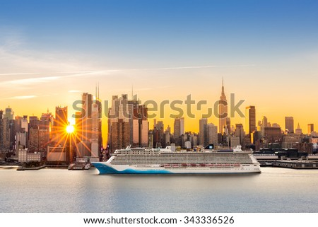 New York City skyline at sunrise, as viewed from Weehawken, along the 42nd street canyon. A large cruise ship sails Hudson river, while sun beams burst between the skyscrapers. - stock photo