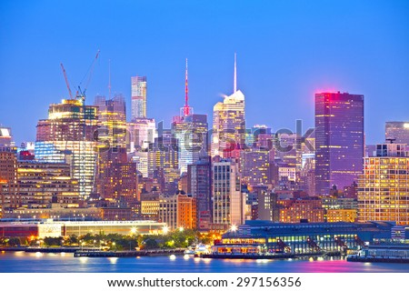 New York City skyline, modern illuminated colorful buildings in downtown Manhattan at sunset - stock photo