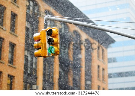 New York city traffic lights with skyscrapers on background during massive snowfall - stock photo