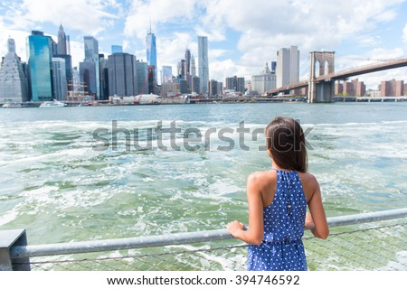 New York city urban woman enjoying view of downtown Manhattan skyline from Brooklyn park living a happy lifestyle walking during summer travel in USA. Female Asian tourist in her 20s. - stock photo