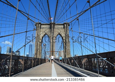 New York City, USA - August 24, 2014: People running and walking across the Brooklyn Bridge with the Lower Manhattan skyline in the background in New York City.  - stock photo