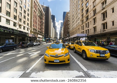 NEW YORK CITY,USA-AUGUST 3, 2013:the famous yellow taxis waiting patiently for pedestrians to pass through the skyscrapers of New York during a sunny day.  - stock photo