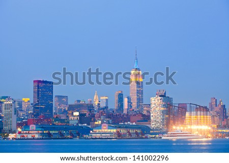 New York City, USA colorful night skyline panorama with illuminated landmark buildings in downtown business and residential districts - stock photo