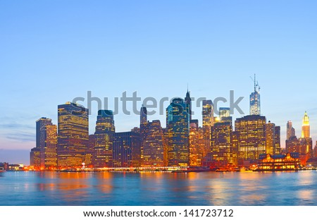New York City, USA colorful sunset skyline panorama with illuminated landmark buildings in downtown financial district