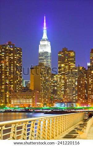 New York City, USA. Downtown buildings in Manhattan with colorful lights, panorama at sunset