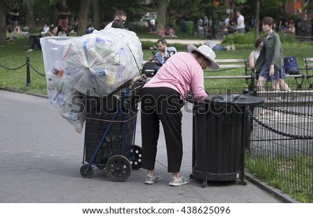 NEW YORK CITY, USA - JUNE 06 2016 - Chinese woman collecting plastic bags and bottles from a trash can in a park in New York, USA