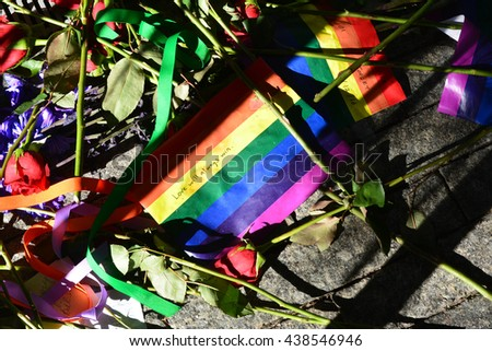 New York City, USA - June 17, 2016: Memorial in Lower Manhattan including flowers and rainbow flag for the victims of the mass shooting in Orlando in 2016 in New York City. - stock photo