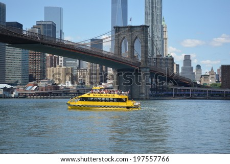 NEW YORK CITY, USA - June 6, 2014: New York Water Taxi cruising in the East River with the Lower Manhattan skyline and Brooklyn Bridge in the background.  - stock photo