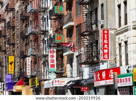 NEW YORK CITY, USA - MAY 26, 2014: Chinese businesses line the streets with signs during a Memorial Day Celebration in Chinatown in Manhattan, New York City. - stock photo