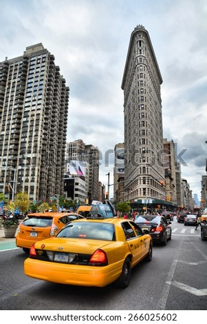 NEW YORK CITY, USA - OCTOBER 18, 2014: Yellow taxi and Flatiron building at Fifth Avenue av in Manhattan. Flatiron is an iconic building of NYC. - stock photo