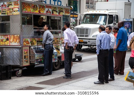 NEW YORK CITY, USA - SEPTEMBER, 2014: Businessmen during lunch at food cart - stock photo