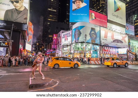 NEW YORK CITY, USA - SEPTEMBER 26: Nightlife at Times Square with crowds of tourists, street performers and Manhattan traffic on September 26, 2014 in NYC. Times Square is an iconic place in USA. - stock photo