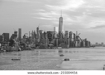 New York City with skyscrapers illuminated over Hudson River panorama, including the One World Trade Center in black and white - stock photo