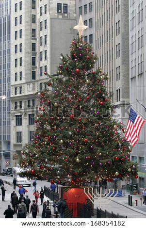 NEW YORK - DEC 19: Pedestrians walk past a Christmas tree near the New York Stock Exchange on Dec  19, 2013 in New York City.  - stock photo
