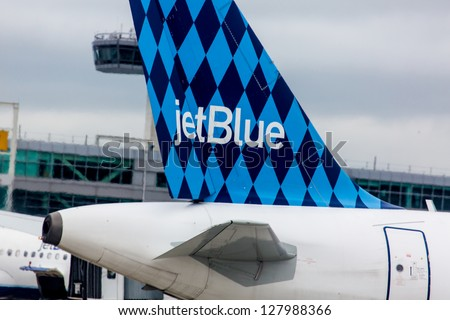 NEW YORK - DECEMBER 9: Airbus A320 JetBlue tailfin Harlequinon design on JFK airport in New York USA on December 9, 2012 JetBlue aircrafts feature one of several tail designs and name with word blue - stock photo
