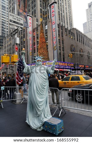 NEW YORK - DECEMBER 19:  Unidentified street performer poses as a Statue of Liberty in the front of  New York City landmark Radio City Music Hall in Rockefeller Center on December 19, 2013. - stock photo