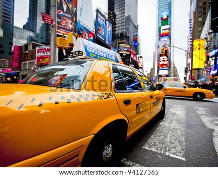 NEW YORK - DECEMBER 17: Yellow cab speeds through Times Square the busy tourist intersection of neon art and commerce and is an iconic street of New York City on Dec 17th, 2011 in New York, NY, USA. - stock photo