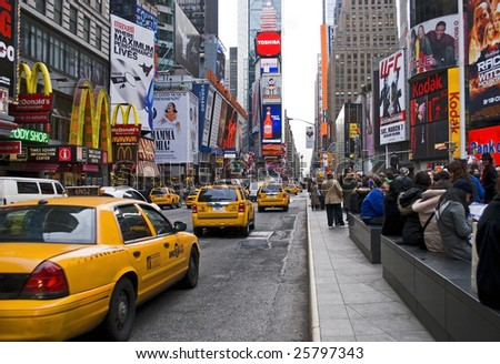 NEW YORK - FEB 27: Taxis move past people in Times Square on February 27, 2009 in New York City. New Plans to ban vehicle traffic on Broadway from 42nd to 47th Streets are scheduled to begin this May. - stock photo