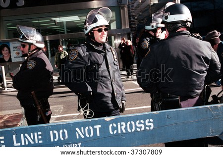 NEW YORK - FEBRUARY 2:  New York City police officers stand guard during a protest march against the World Economic Forum (WEF) February 2, 2002 in New York City. - stock photo