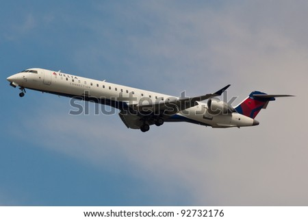 NEW YORK - JANUARY 3:Canadair CL-600 Delta Connection on final approach to JFK in New York on January 3, 2012 is individually owned regional airlines operate short and medium as a Delta Air Lines - stock photo