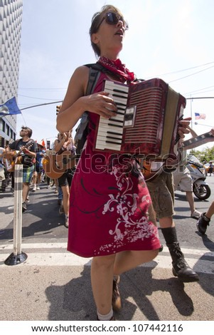 NEW YORK-JULY 11: An Occupy Guitarmy protester plays an accordion during the #99MileMarch from Philly to NYC on July 11, 2012 in New York, NY. - stock photo
