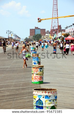 NEW YORK - JULY 16: Coney Island's boardwalk on July 16, 2011 in New York. Coney Island boardwalk, a strip on the Atlantic Ocean in southern Brooklyn, N.Y. is populated with amusement parks and shops. - stock photo