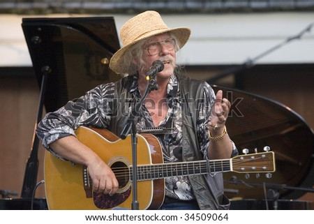 NEW YORK - JULY 30: Musician Arlo Guthrie gestures as he performs at Battery Park's Castle Clinton on July 30, 2009 in New York City. - stock photo