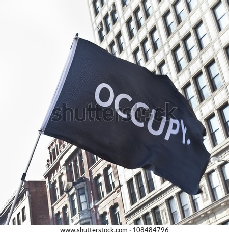 NEW YORK - JULY 24: Occupy Wall Street movement black flag waved on Union Square in Manhattan on July 24, 2012 in New York. - stock photo