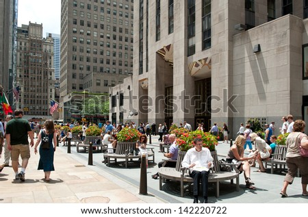 NEW YORK - JULY 3: people at the base of Rockefeller Center on July 3, 2012 in New York. It was built by the Rockefeller family in 1939 and was declared a National Historic Landmark in 1987. - stock photo
