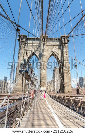 NEW YORK - JULY 17: People walk on Brookly Bridge in New York City on July 17, 2014. The Brooklyn Bridge is a bridge in New York City and is one of the oldest suspension bridges in the United States.