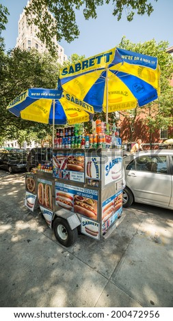 NEW YORK - JUNE 16: hot dog vendor by Washington Square Park on June 16, 2014 in New York. Washington Square Park is one of the best-known of New York City's 1,900 public parks. - stock photo