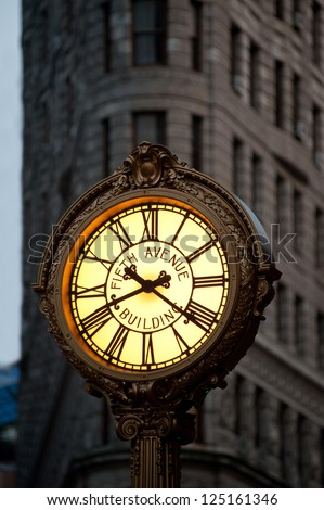 NEW YORK - JUNE 28: Sidewalk clock at 200 Fifth Avenue (1909) with Flatiron building facade on June, 28th 2012 in NY. Completed in 1902, it is considered to be one of the first skyscrapers ever built. - stock photo