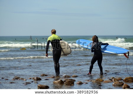 NEW YORK-JUNE 13: Unidentified women surfers with surfboard on Ditch Plains surfing beach go to surf in Montauk, New York in the Hamptons on June 13, 2015. - stock photo