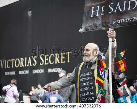 NEW YORK - MAR 27 2016: A man holding a religious sign stands on 5th Avenue in front of Victorias Secret on Easter Sunday during the traditional Easter Bonnet Parade in Manhattan on March 27, 2016. - stock photo