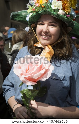 NEW YORK - MAR 27 2016: A woman wearing an Easter bonnet made of flowers holds a large rose on Easter Sunday during the traditional Easter Bonnet Parade along 5th Ave in Manhattan on March 27, 2016. - stock photo
