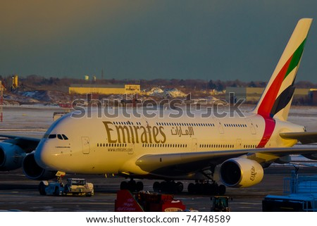 NEW YORK - MARCH 1: Airbus A380 Emirates taxing to the gate on JFK Airport in new York, USA on March 1, 2011. As of 2011 A380 is the biggest plane ever used in commercial passenger transportation - stock photo