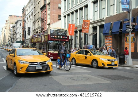 NEW YORK - MARCH 10, 2016: New York City Taxi and Citibike rider in Soho, Lower Manhattan - stock photo