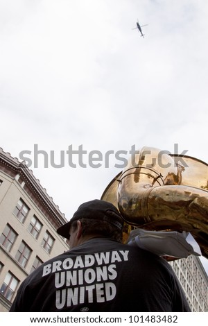 NEW YORK - MAY 1: A musician wearing a t-shirt that says 'Broadway Unions United' holds a tuba during May Day protests in Bryant Park on May 1, 2012 in New York, NY. A police helicopter hovers above. - stock photo